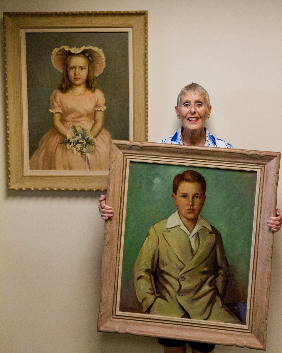 Jane Quigley with her portrait holding that of her brother Lawrence M. Quigley